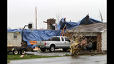 People work to cover the holes in a roof after severe weather damaged homes on Plymouth Springmill Road just south of the intersection of Ohio Route 96 in Shelby, Ohio, Sunday, April 14, 2019. (Tom E. Puskar/The Times Gazette via AP)