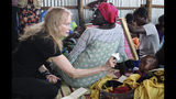 In this photo taken Tuesday, April 2, 2019, human rights activist Mia Farrow plays with a baby lying on his mother's lap while speaking to a group of women during a visit to an internally displaced person's camp in the capital Juba, South Sudan. Human rights activist Mia Farrow spoke to The Associated Press as she visited South Sudan again in her new role as envoy for the International Rescue Committee, helping the aid group to promote a global initiative to change the way humanitarian organizations approach malnutrition. (AP Photo/Sam Mednick)