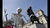 A skeleton is carried past the Winston Churchill statue as demonstrators take part in a 'Funeral Procession' during a climate protest in Parliament Square in London, Monday, April 15, 2019. Extinction Rebellion have organised a nationwide week of action, they are calling for a full-scale Rebellion to demand decisive action from governments on climate change and ecological collapse. They plan to engage in acts of non-violent civil disobedience against governments in capital cities around the world.(AP Photo/Kirsty Wigglesworth)
