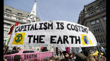 Protesters take part holding placards during a climate change demonstration in London, Monday, April 15, 2019. Extinction Rebellion have organised a nationwide week of action, they are calling for a full-scale Rebellion to demand decisive action from governments on climate change and ecological collapse. They plan to engage in acts of non-violent civil disobedience against governments in capital cities around the world. (AP Photo/Alastair Grant)