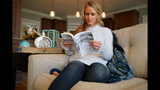 "In this Wednesday, March 27, 2019, photo, Kacey Ruegsegger Johnson pages through a copy of her memoir at her home in Cary, N.C. The book, ""Over My Shoulder,"" recounts her physical, emotional and spiritual recovery following the 1999 massacre of Colorado's Columbine High School. (AP Photo/Allen G. Breed)"