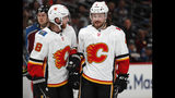 Calgary Flames center Elias Lindholm, left, confers with defenseman Rasmus Andersson in the second period of Game 3 of a first-round NHL hockey playoff series against the Colorado Avalanche, Monday, April 15, 2019, in Denver. (AP Photo/David Zalubowski)