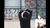 A man stretches in front of an electronic stock board of a securities firm in Tokyo, Tuesday, April 16, 2019. Shares were mixed Tuesday in Asia in mostly narrow trading in the absence of any major market-driving news.(AP Photo/Koji Sasahara)
