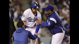 Los Angeles Dodgers' Cody Bellinger, center, winces after being hit in the knee by a pitch as a trainer and manager Dave Roberts tend to him during the third inning of a baseball game, Monday, April 15, 2019, in Los Angeles. (AP Photo/Mark J. Terrill)