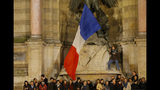 People attend a vigil in Paris, Tuesday April 16, 2019. Firefighters declared success Tuesday in a more than 12-hour battle to extinguish an inferno engulfing Paris' iconic Notre Dame cathedral that claimed its spire and roof, but spared its bell towers and the purported Crown of Christ. (AP Photo/Michel Euler)
