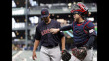 Cleveland Indians catcher Roberto Perez, right, gives starting pitcher Carlos Carrasco a pat as they head into the dugout after the third inning of a baseball game against the Seattle Mariners on Wednesday, April 17, 2019, in Seattle. (AP Photo/Elaine Thompson)