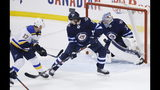 St. Louis Blues' Jaden Schwartz (17) scores the against Winnipeg Jets goaltender Connor Hellebuyck (37) as Jets' Jacob Trouba (8) defends in the final minute of Game 5 of an NHL hockey first-round playoff series Thursday, April 18, 2019, in Winnipeg, Manitoba. (John Woods/The Canadian Press via AP)