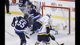 St. Louis Blues' Brayden Schenn (10) scores the tying goal against Winnipeg Jets goaltender Connor Hellebuyck (37) during the third period of Game 5 of an NHL hockey first-round playoff series Thursday, April 18, 2019, in Winnipeg, Manitoba. (John Woods/The Canadian Press via AP)