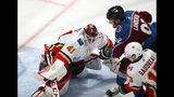 Calgary Flames goaltender Mike Smith, left, stops a shot by Colorado Avalanche left wing Gabriel Landeskog, back right, who drives by Calgary left wing Johnny Gaudreau during the first period of Game 4 of an NHL hockey playoff series Wednesday, April 17, 2019, in Denver. (AP Photo/David Zalubowski)