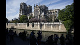 """People watch Notre Dame cathedral, in Paris, Wednesday, April 17, 2019. Notre Dame Cathedral would have been completely burned to the ground in a """"chain reaction collapse"""" had firefighters not moved rapidly in deploying their equipment to battle the blaze racing through the landmark monument, a Paris official said Wednesday. (AP Photo/Thibault Camus)"""