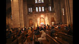 Worshippers stay in silence while bells toll during a mass at the Basilica of the Sacred Heart of Paris, Wednesday, April 17, 2019. The bells of France have tolled, ringing out from the nation's cathedrals and basilicas in commemoration of the Notre Dame fire. (AP Photo/Francisco Seco)