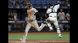 Baltimore Orioles' Joey Rickard (23) scores on a single by Richie Martin as Tampa Bay Rays catcher Mike Zunino (10) leaps for a high throw during the seventh inning of a baseball game Thursday, April 18, 2019, in St. Petersburg, Fla. (AP Photo/Chris O'Meara)