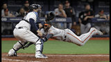 Baltimore Orioles' Jonathan Villar, right, goes airborne as he scores in front of Tampa Bay Rays catcher Mike Zunino on a sacrifice fly by Dwight Smith Jr. during the eighth inning of a baseball game Thursday, April 18, 2019, in St. Petersburg, Fla. (AP Photo/Chris O'Meara)