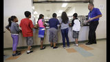 """FILE - In this Sept. 10, 2014, file photo, detained immigrant children line up in the cafeteria at the Karnes County Residential Center, a detention center for immigrant families, in Karnes City, Texas. The Trump administration stopped using the center to hold parents and children in March 2019. It's cut back on family detention even as it complains it has to """"catch and release"""" migrant families, many of them Central American parents and children who seek asylum. (AP Photo/Eric Gay, File)"""