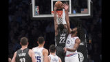 Brooklyn Nets guard Caris LeVert (22) dunks past Philadelphia 76ers center Joel Embiid (21) during the first half of of Game 4 of a first-round NBA basketball playoff series, Saturday, April 20, 2019, in New York. (AP Photo/Mary Altaffer)