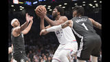 Philadelphia 76ers center Joel Embiid (21) goes to the basket against Brooklyn Nets guard D'Angelo Russell (1)and forward Jared Dudley during the first half of of Game 4 of a first-round NBA basketball playoff series, Saturday, April 20, 2019, in New York. (AP Photo/Mary Altaffer)