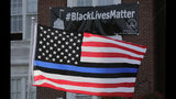 """FILE - In this July 28, 2016, file photo, a flag with a blue and black stripes in support of law enforcement officers, flies at a protest by police and their supporters outside Somerville City Hall in Somerville, Mass. An Oregon county has agreed to pay $100,000 to a black employee who sued after a co-worker pinned up a """"Blue Lives Matter"""" flag. The Oregonian/OregonLive reports Saturday, April 20, 2019, that Karimah Guion-Pledgure alleged in her January lawsuit that the flag demeans the """"Black Live Matter"""" movement. (AP Photo/Charles Krupa, File)"""