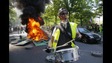A man bangs a drum in front of a fire on the street during a yellow vest demonstration in Paris, Saturday, April 20, 2019. French yellow vest protesters are marching anew to remind the government that rebuilding the fire-ravaged Notre Dame Cathedral isn't the only problem the nation needs to solve. (AP Photo/Michel Euler)
