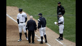 New York Yankees' Aaron Judge, left, reacts while talking to a trainer and bench coach Josh Bard, center, after hitting a single to right field during the sixth inning of a baseball game against the Kansas City Royals, Saturday, April 20, 2019, in New York. Judge left the game with an apparent injury. (AP Photo/Julio Cortez)
