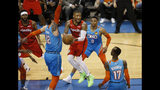 Portland Trail Blazers' Damian Lillard center, looks for someone to pass to, between Oklahoma City Thunder center Steven Adams (12), guard Russell Westbrook (0) and and guard Dennis Schroeder (17) during the first half of Game 3 of an NBA basketball first-round playoff series Friday, April 19, 2019, in Oklahoma City. (AP Photo/Sue Ogrocki)
