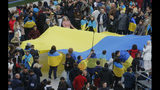 People hold Ukrainian national flag at the Olympic stadium prior debates between two candidates in the weekend presidential run-off in Kiev, Ukraine, Friday, April 19, 2019. Friday is the last official day of election canvassing in Ukraine as all presidential candidates and their campaigns will be barred from campaigning on Saturday, the day before the vote. (AP Photo/Efrem Lukatsky)