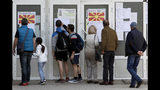 """People check lists before voting in the presidential election outside a polling station in Skopje, North Macedonia, Sunday, April 21, 2019. Polls were opened early on Sunday in North Macedonia for presidential elections seen as key test of the government following deep polarization after the country changed its name to end a decades-old dispute with neighboring Greece over the use of the term """"Macedonia"""". (AP Photo/Boris Grdanoski)"""