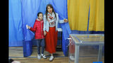 A woman and her daughter, left, leave a booth at a polling station during the second round of presidential elections in Kiev, Ukraine, Sunday, April 21, 2019. Top issues in the election have been corruption, the economy and how to end the conflict with Russia-backed rebels in eastern Ukraine. (AP Photo/Vadim Ghirda)