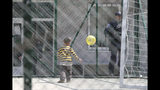 A child plays with a ball near a police officer at a detention center where authorities have brought back from Syria 110 Kosovar citizens, mostly women and children in the village of Vranidol on Sunday, April 20, 2019. Four suspected fighters have been arrested, but other returnees will be cared for, before being sent to homes over the coming days according to Justice Minister Abelard Tahiri. (AP Photo/Visar Kryeziu)