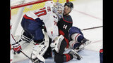 Carolina Hurricanes' Justin Williams (14) collides with Washington Capitals goalie Braden Holtby (70) during the second period of Game 6 of an NHL hockey first-round playoff series in Raleigh, N.C., Monday, April 22, 2019. (AP Photo/Gerry Broome)