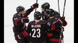 Carolina Hurricanes' Brett Pesce (22), Brock McGinn (23), Justin Williams, and Jordan Staal, top right, celebrate Williams' goal against the Washington Capitals during the third period of Game 6 of an NHL hockey first-round playoff series in Raleigh, N.C., Monday, April 22, 2019. (AP Photo/Gerry Broome)