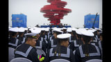 Chinese sailors sit during a concert featuring Chinese and foreign military bands in Qingdao, Monday, April 22, 2019. Ships from Chinese and foreign navies have gathered in Qingdao for events this week, including a naval parade, to mark the 70th anniversary of the founding of the People's Liberation Army (PLA) Navy. (AP Photo/Mark Schiefelbein)