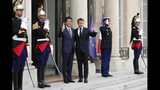 French President Emmanuel Macron, center right, and Japan's Prime Minister Shinzo Abe wave before their talks at the Elysee Palace, Tuesday, April 23, 2019 in Paris. (AP Photo/Thibault Camus)