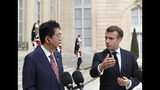 French President Emmanuel Macron, right, welcomes Japan's Prime Minister Shinzo Abe before their talks at the Elysee Palace, Tuesday, April 23, 2019 in Paris. (AP Photo/Thibault Camus)