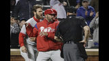 Philadelphia Phillies manager Gabe Kapler, center, restrains Bryce Harper, left, while arguing a call with umpire Mark Carlson during the fourth inning of a baseball game Monday, April 22, 2019, in New York. (AP Photo/Frank Franklin II)