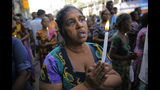 Sri Lankans pray during a three minute nationwide silence observe to pay homage to the victims of Easter Sunday's blasts outside St. Anthony's Shrine in Colombo, Sri Lanka, Tuesday, April 23, 2019. A state of emergency has taken effect giving the Sri Lankan military war-time powers not used since civil war ended in 2009. Police arrested 40 suspects, including the driver of a van allegedly used by suicide bombers involved in deadly Easter bombings. (AP Photo/Eranga Jayawardena)