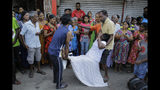 People carry a woman who fainted during a three minute nationwide silence, observe to pay homage to the victims of Easter Sunday's blasts outside St. Anthony's Shrine in Colombo, Sri Lanka, Tuesday, April 23, 2019. A state of emergency has taken effect giving the Sri Lankan military war-time powers not used since civil war ended in 2009. Police arrested 40 suspects, including the driver of a van allegedly used by suicide bombers involved in deadly Easter bombings. (AP Photo/Eranga Jayawardena)