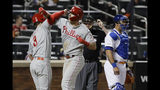 New York Mets catcher Wilson Ramos, right, looks away as Philadelphia Phillies' Bryce Harper, left, celebrates with Rhys Hoskins, center, after Hoskins hit a two-run home run during the ninth inning of a baseball game, Wednesday, April 24, 2019, in New York. (AP Photo/Frank Franklin II)