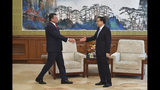 European Commission Vice President Maros Sefcovic, left, approaches to shake hands with Chinese Premier Li Keqiang before their meeting at the Diaoyutai State Guesthouse in Beijing Thursday, April 25, 2019. (Parker Song/Pool Photo via AP)