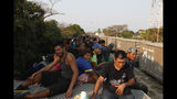 Central American migrants ride atop a freight train during their journey toward the US-Mexico border, in Ixtepec, Oaxaca State, Mexico, Tuesday, April 23, 2019. It's not as if the migrants think the train is safe; they acknowledge the dangers of riding through the darkness perched high atop the freight cars. (AP Photo/Moises Castillo)