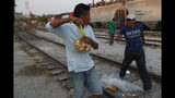 """Central American migrants grab bags of bread before climbing on a north bound freight train during their journey toward the US-Mexico border, in Ixtepec, Oaxaca State, Mexico, Tuesday, April 23, 2019. Just like increased U.S. border protection, Mexico's increased enforcement efforts push migrants into using more dangerous means of travel, like the freight trains running north known to them as """"La Bestia"""". (AP Photo/Moises Castillo)"""