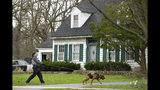 """A blood hound K-9 officer and his handler sniffs the ground in front of the home of 5-year-old Andrew """"AJ"""" Freund on Thursday, April 18, 2019 in Crystal Lake, Ill. Crystal Lake police said Friday that they have no indication Andrew """"AJ"""" Freund was abducted. They say canine units only picked up the boy's scent within the residence, which indicates Andrew didn't leave on foot. Police say Andrew's parents last saw him about 9 p.m. Wednesday and reported him missing Thursday when they woke up and couldn't find him in the home. (Stacey Wescott/Chicago Tribune via AP)"""
