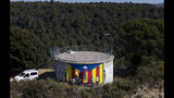 """In this Sunday, March 24, 2019 photo, activists paint an """"estelada"""" or independence flag on a water tank near Barcelona, Spain. A substantial pool of undecided voters and a right-wing splintered by a rising populist party are making confident predictions harder to come by as Spain prepares for its third parliamentary election in less than four years. (AP Photo/Emilio Morenatti)"""