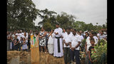 "Sri Lankan Roman Catholic priests Father Anthony Nishan participates in a funeral service of a victim of Easter Sunday's church explosion of Katuwapitiya in Colombo, Sri Lanka, Thursday, April 25, 2019. There are 41 dirt mounds piled with flowers and candles, with wooden crosses marked mostly with numbers that correspond to names in a book that the priests keep. There's fear of more violence and deep grief in this majority Christian enclave outside Colombo. ""The whole village is a funeral. The houses here are filled with coffins,"" Nishan said of a place where about 120 Christians died in the bombing. (AP Photo/Manish Swarup)"