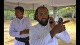 Sri Lankan Roman Catholic priests Father Niroshan Perera, right, speaks on his mobile phone with Father Anthony Nishan standing behind him at a mass burial ground for Easter Sunday's church explosion victims of Katuwapitiya in Colombo, Sri Lanka, Thursday, April 25, 2019. Christians in Sri Lanka belong to both its main ethnic groups, and that rare inclusiveness of a small religious minority may explain the measured calm that's been the response so far to the Easter attacks. But there's widespread fear that more attacks could plunge Sri Lanka into the cycle of violence and retaliation that marked the bloody civil war that ended a decade ago. (AP Photo/Manish Swarup)