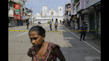 A Sri Lankan ethnic Tamil woman walks on a road leading to St. Anthony's Church, one of the sites of Easter Sunday's bomb attacks in Colombo, Sri Lanka, Thursday, April 25, 2019. Christians in Sri Lanka belong to both its main ethnic groups, and that rare inclusiveness of a small religious minority may explain the measured calm that's been the response so far to the Easter attacks. But there's widespread fear that more attacks could plunge Sri Lanka into the cycle of violence and retaliation that marked the bloody civil war that ended a decade ago. (AP Photo/Eranga Jayawardena)