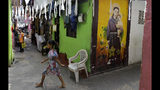 A Sri Lankan child walks past a graffiti of St. Anthony at a neighborhood near St. Anthony's Church, one of the sites of the Easter Sunday bombings, in Colombo, Sri Lanka, Thursday, April 25, 2019. Christians in Sri Lanka belong to both its main ethnic groups, and that rare inclusiveness of a small religious minority may explain the measured calm that's been the response so far to the Easter attacks. But there's widespread fear that more attacks could plunge Sri Lanka into the cycle of violence and retaliation that marked the bloody civil war that ended a decade ago. (AP Photo/Eranga Jayawardena)