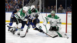 St. Louis Blues center Tyler Bozak (21) has his shot blocked by Dallas Stars' Ben Bishop (30) who receives help from defenseman Ben Lovejoy (21) defending the net during the second period in Game 1 of an NHL second-round hockey playoff series Thursday, April 25, 2019, in St. Louis. (AP Photo/Jeff Roberson)