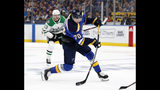 St. Louis Blues center Oskar Sundqvist (70) takes a shot as Dallas Stars' Mattias Janmark (13) looks on during the second period in Game 1 of an NHL second-round hockey playoff series Thursday, April 25, 2019, in St. Louis. (AP Photo/Jeff Roberson)