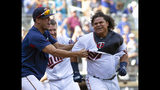 """FILE - In this Sept. 9, 2018, file photo, Minnesota Twins' Willians Astudillo, right, is mobbed by teammate Jose Berrios after hitting a 2-run home run during the ninth inning of a baseball game against the Kansas City Royals, in Minneapolis. The most popular player on the first-place Minnesota Twins is the third-string catcher and versatile everyman Willians Astudillo, whose all-out style has endeared him to the team and the fans since his debut last season. His cult hero status reaches a new high on Friday night, when the Twins give away """"La Tortuga"""" T-shirts in honor of his nickname, which means turtle in Spanish, at their game against Baltimore. (AP Photo/Paul Battaglia, File)"""