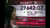 A woman walks past a bank electronic board showing the Hong Kong share index at Hong Kong Stock Exchange Friday, April 26, 2019. Shares were mostly lower in Asia on Friday after an overnight decline on Wall Street spurred by disappointingly weak earnings reports from 3M and other industrial companies. (AP Photo/Vincent Yu)